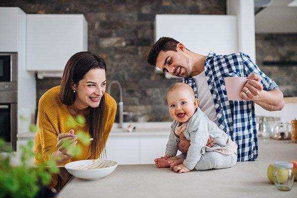 Perhe vauvan kanssa kotona