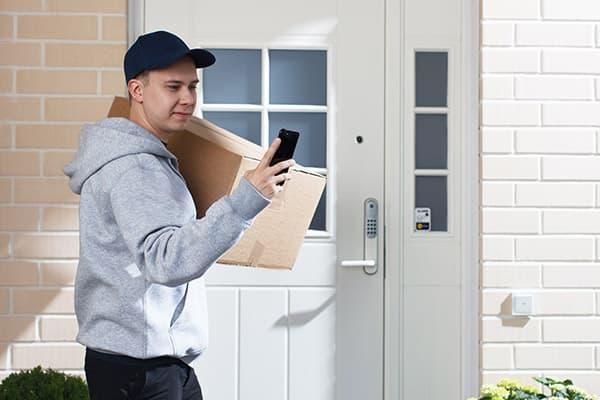Postinkantaja paketin kanssa ulko-oven edessä