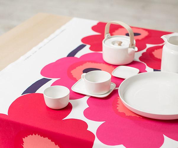 Punainen unikko-pöytäliina ja valkoisia oiva-astioita