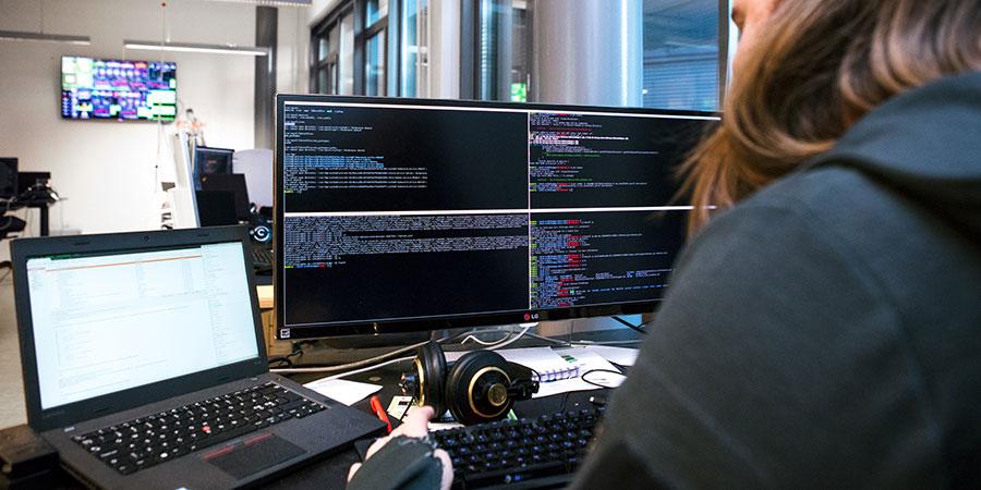 Työntekijä tietokoneen edessä koodaamassa