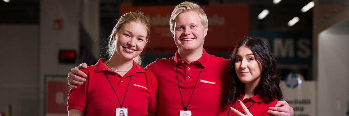 Verkkokauppa.comin hymyileviä työntekijöitä punaisissa paidoissaan