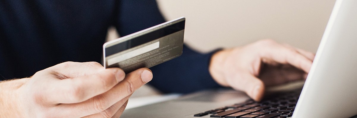 Yrittäjä istuu tietokoneella ja maksaa käyttäen luottokorttia