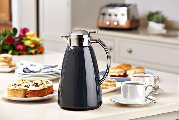 Termoskannu, kahvikuppeja sekä leivonnaisia pöydällä