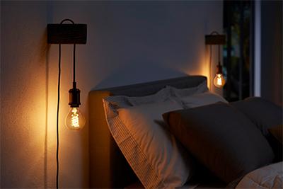 Tunnelmalliset Philips Hue -lamput sängyn vieressä