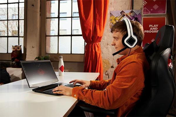 Mies pelaa Omen-kannettavalla Omen-kuulokkeet päässä