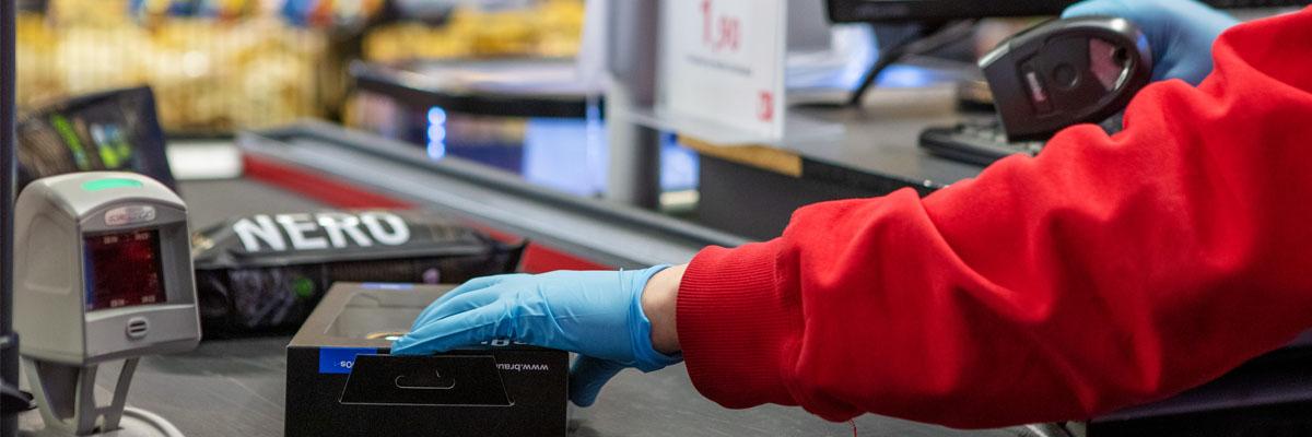 Myyjä käsittelee tuotteita kassalla hanskat kädessä