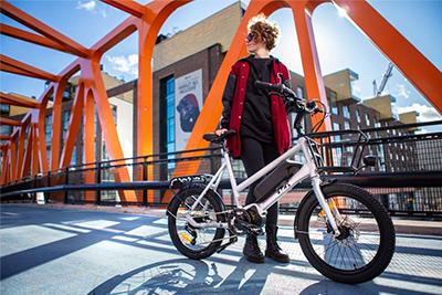 Kaupunkisähköpyörä auringossa ja onnellinen pyöräilijä